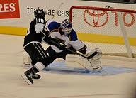 """A goalie """"catches"""" the """"puck"""" in his glove."""
